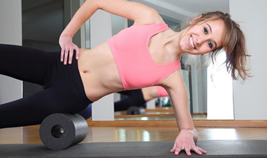 Frau auf Gymnastikrolle seitlich am Boden
