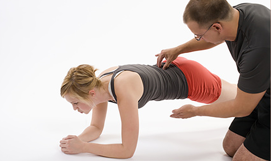 Female client working out with fitness trainer